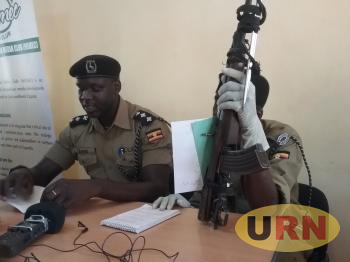 Police Public Relations Officer Jimmy Patrick Okema (L) Displays the Recovered Weapon