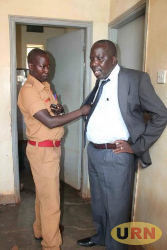 Ocen being searched by a prison warder at the court cell.