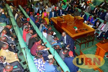 State Minister for Water Ronald Kibuule interacts with Opposition Members of Parliament.