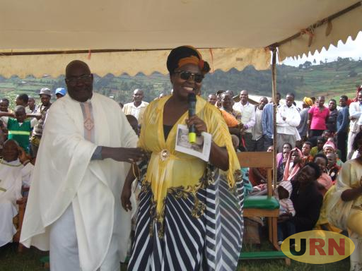 Fr. Gaetano Batanyenda attempting to grab the microphone from Ruth Nankabirwa.