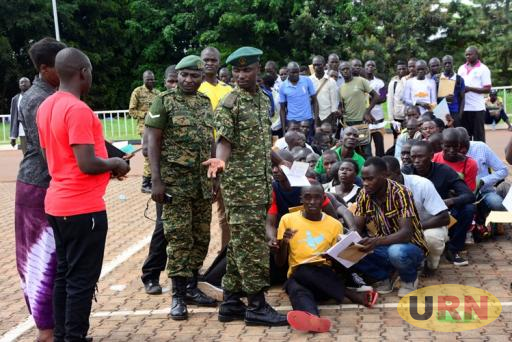 A UPDF Officer Mpangire struggles to chase away his fellow officer identified as Kekikomo and other parents as he checked the academic documents of the prospective recruits.