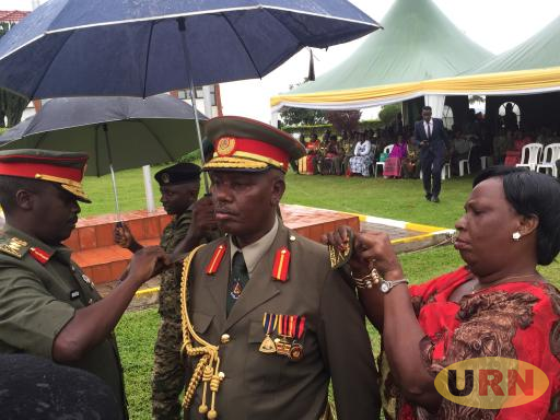 Major General Stephen Rwabantu Tumusiime the Deputy commander Reserve Forces Is decorated by CDF David Muhoozi and his wife at the function held at Defense Headquarters