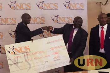 NCS Board chairman Bosco Onyik (R) hands over a dummy cheque of 50 million Uganda Shelling to Cheptegei.