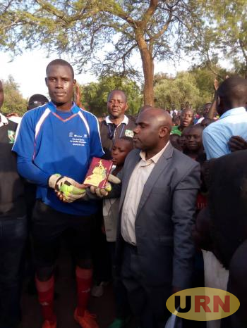 Anthony Mwesigye, the commissioner of the match hands over a gift to Rajab Kajoba, from Karamoja Province who was voted the best player of the day.