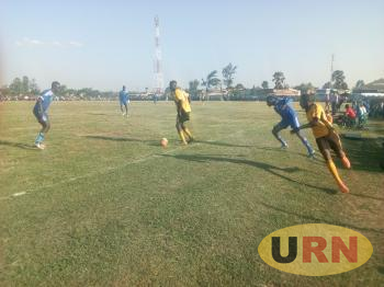 A Bugisu team player (in yellow) and West Nile player (in Blue) dash off the touch line as they position themselves to receive a goal pass at Green Light stadium on Saturday