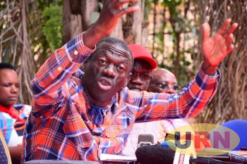 Dr. Kizza Besigye, the former Forum for Democratic Change (FDC) Party President addresses Journalists as the current FDC Party President Patrick Amuriat Oboi looks on in the back ground.