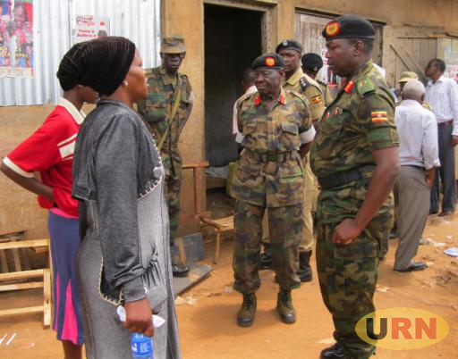 The Chief of Staff Land Forces Major General Charles Angina,Bombo Camp Commandant Brigadier Hussein Adda looking to an a child who lost her mother in the attack.They were standing at entrance of the bar were her mother Amina Aseru was shot dead.